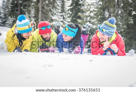 Group of friends lying down in the snow and having fun. Winter vacations and good mood - stock photo