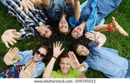 Group of friends lying on meadow - stock photo