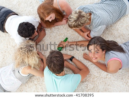 Group of friends lying on the floor and playing spin the bottle - stock photo