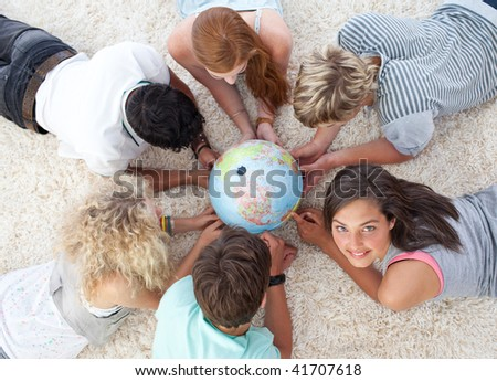 Group of friends lying on the floor examining a terrestrial world - stock photo