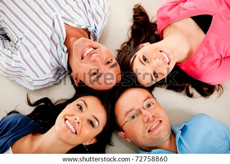 Group of friends lying on the floor with heads together
