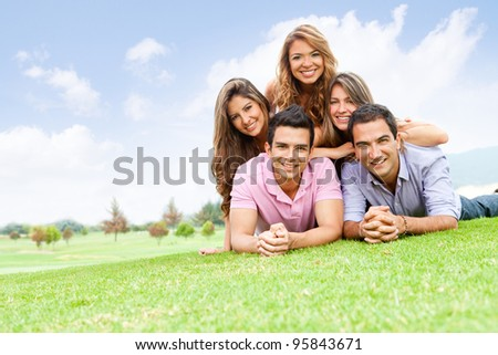 Group of friends lying outdoors having fun - stock photo