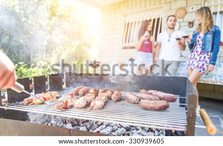 group of friends making a barbecue in the backyard garden.one person is cooking and grilling. the rest of the group is having fun drinking wine. Focus on the cooked sausages - stock photo
