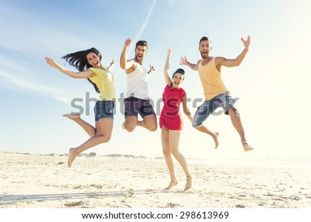 Group of friends making a jump together at the beach - stock photo