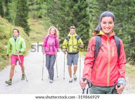 group of friends making trekking excursion in the forest. concept about seasonal leisure activity,nature, and people - stock photo