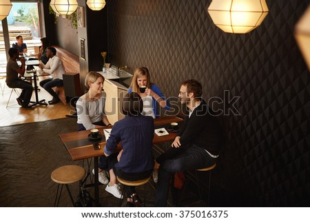 Group of friends meeting for cappucinos in a coffee shop - stock photo