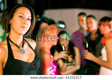 Group of friends - men and women of different ethnicity - having fun in a disco or nightclub drinking; beautiful colored woman in front - stock photo