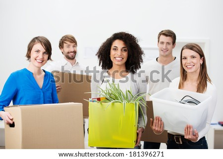 Group of friends moving house working as a team carrying boxes and packages of household items as they stand grouped together smiling at the camera - stock photo