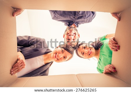 Group of friends moving to new apartment and unpacking boxes -  Happy people looking inside a box - stock photo