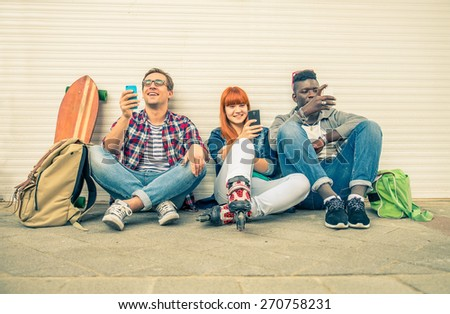 Group of friends of different ethnics sitting on the street and looking at phone - Young hipster people having fun with new technologies - Multiracial group representing the addiction to technology - stock photo