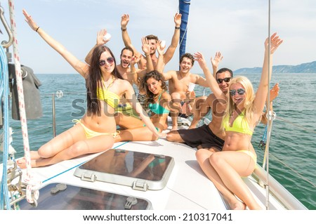 Group of friends on a boat having fun - stock photo