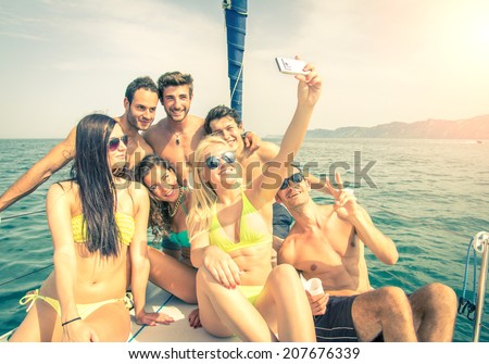 Group of friends on a boat taking a selfie - stock photo