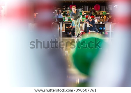 Group of friends on an active night out, bowling in a bowling alley, seen from the point of view of the pins - stock photo