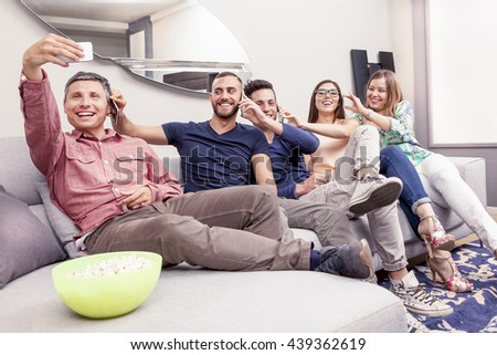 group of friends on couch takes a selfie in a funny way