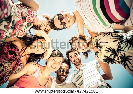 Group of friends on the beach in a sunny day. Concept about mixed race friends and vacations