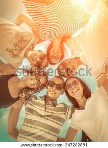 Group of friends on the beach under sunlight. - stock photo