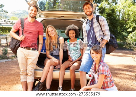 Group Of Friends On Trip Sitting In Trunk Of Car - stock photo