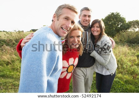 Group Of Friends On Walk In Autumn Countryside Together - stock photo