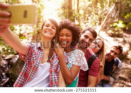 Group Of Friends On Walk Taking Selfie In Forest - stock photo
