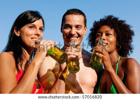 Group of friends - one man embraces two women and all have drinks in swimwear on the beach of a lake in summer