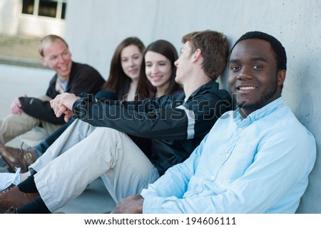 Group of friends outside on campus - stock photo