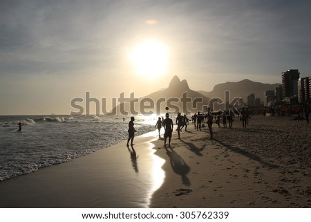 Group of friends playing soccer at Ipanema Beach in sunset.