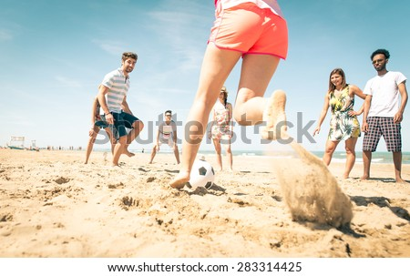 group of friends playing soccer on the beach. a girl is shooting to score a goal. concept about friends, sport, vacations and people - stock photo