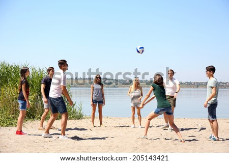 Group of friends playing volleyball at beach - stock photo