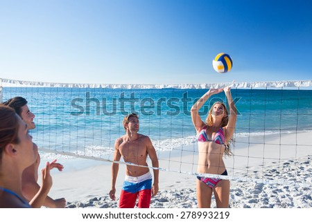 Group of friends playing volleyball at the beach - stock photo
