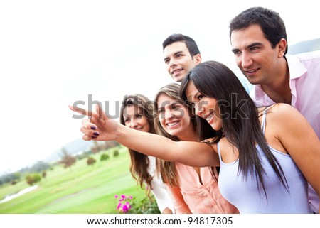 Group of friends pointing with finger outdoors
