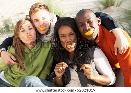 Group Of Friends Pulling Funny Faces On Beach - stock photo
