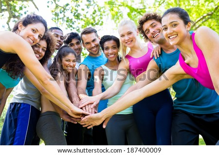 Group of friends putting their hands together in the park - stock photo