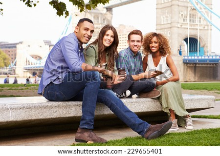 Group Of Friends Relaxing By Tower Bridge In London - stock photo