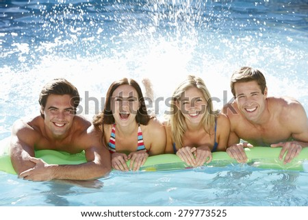 Group Of Friends Relaxing In Swimming Pool Together - stock photo