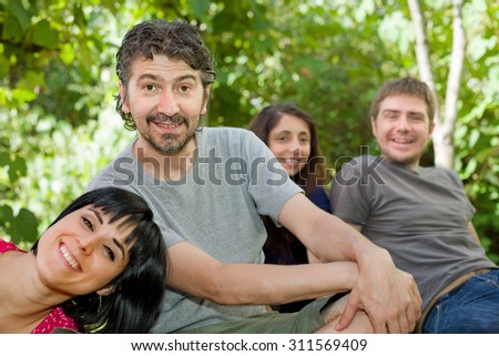 group of friends relaxing outdoors, focus on the man on the left - stock photo