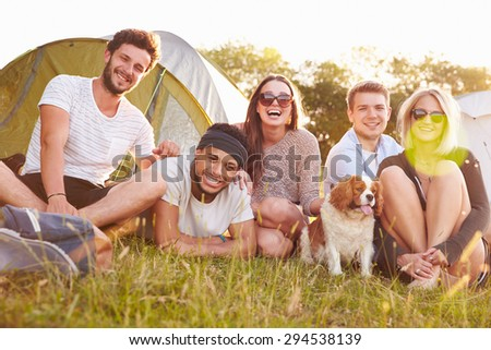 Group Of Friends Relaxing Outside Tents On Camping Holiday - stock photo