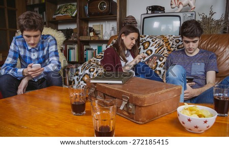 Group of friends relaxing using digital devices in a bored day at home. Teenager leisure time concept. - stock photo