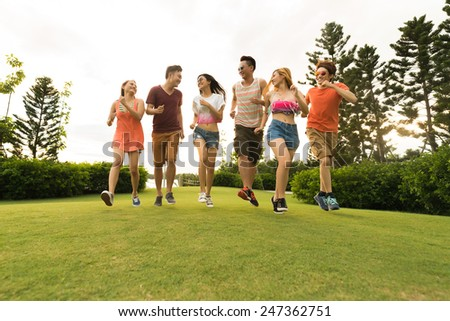 Group of friends running on summer meadow - stock photo