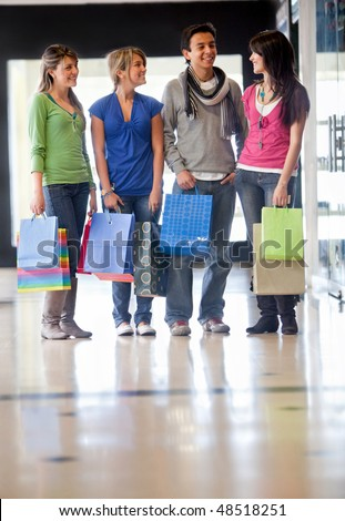 Group of friends shopping in a mall with some bags