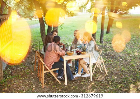 Group of friends sitting by Thanksgiving table outdoors - stock photo