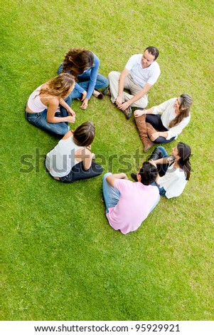 Group of friends sitting in a circle and talking - outdoors - stock photo