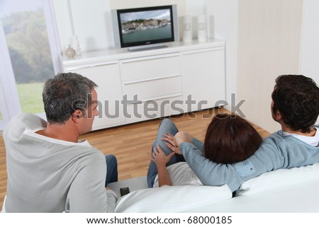 Group of friends sitting in sofa watching tv - stock photo