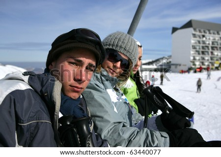 Group of friends sitting on a chairlift - stock photo