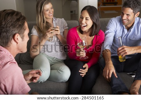 Group Of Friends Sitting On Sofa Talking And Drinking Wine