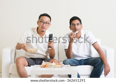Group of friends sitting on sofa watching football match on television together at home. - stock photo