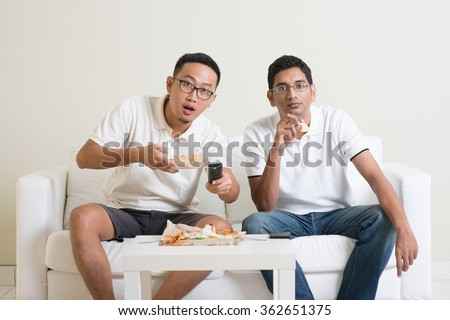Group of friends sitting on sofa watching football match together at home. - stock photo
