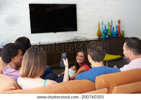 Group Of Friends Sitting On Sofa Watching TV Together - stock photo