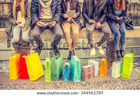 Group of friends sitting outdoors with shopping bags - Several people holding smartphones and tablets - Concepts about lifestyle,shopping,technology and friendship - stock photo