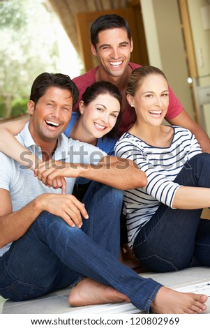 Group Of Friends Sitting Outside House - stock photo