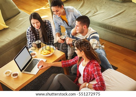 Group of friends sitting together in living room and watching movie on on laptop.Home party.